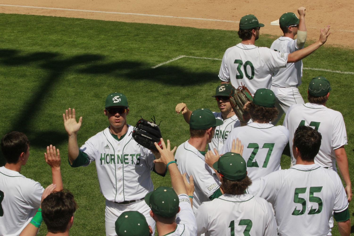 Sac State outfielders junior Matt Smith (left) and senior Bronson Grubbs (right) high-five teammates upon returning to the dugout in a 5-4 win Sunday over CSU Bakersfield at John Smith Field. Since beginning the season 3-6, the Hornets have gone 18-4 and are currently first in the Western Athletic Conference.