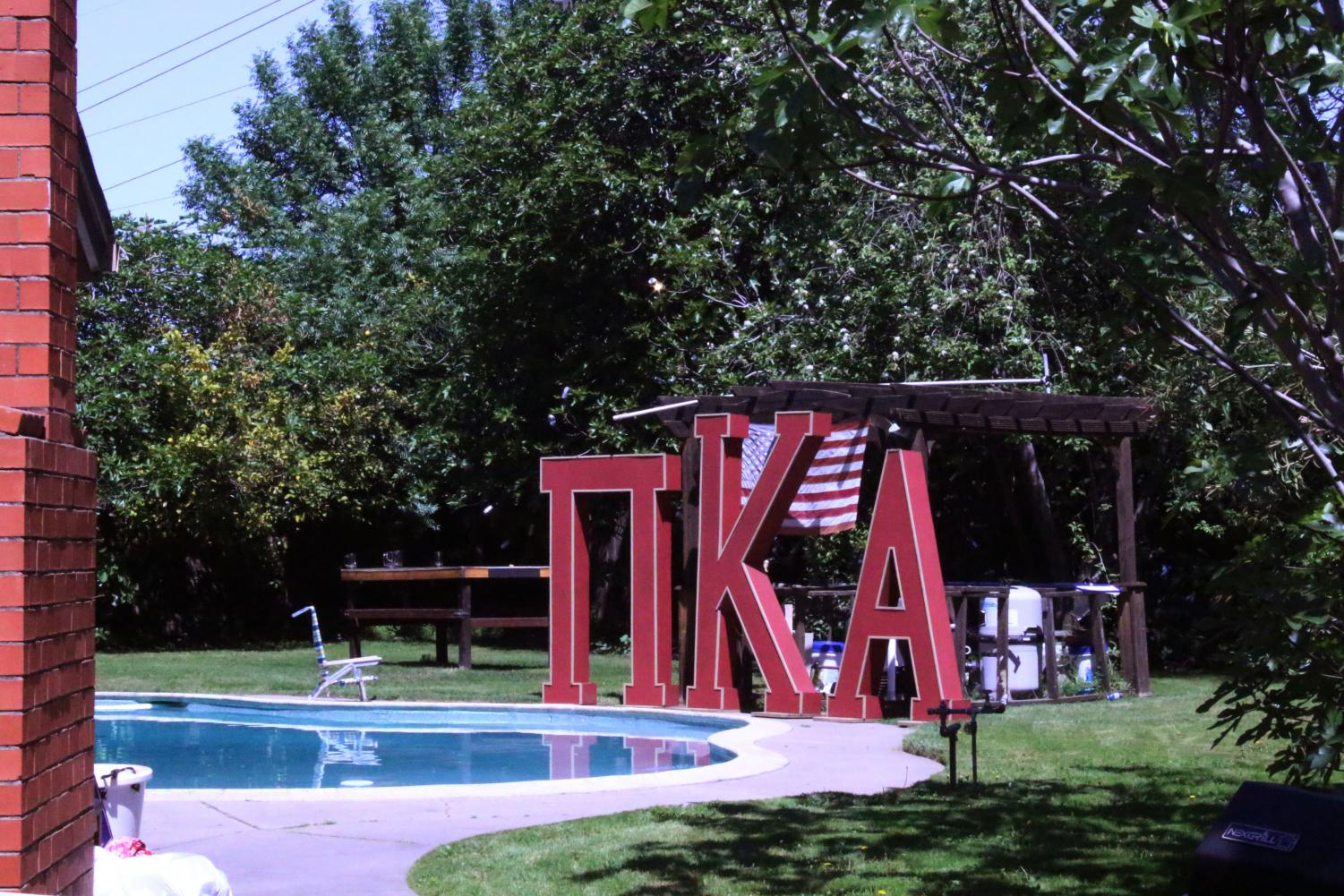 Large Greek letters are visible next to a backyard pool over the fence of the home where 21-year-old Sac State business major and Pi Kappa Alpha member William Molina died after being shot by a pellet gun Friday, April 12. Members of the university's chapter refer to the home as 'The Fratican.'