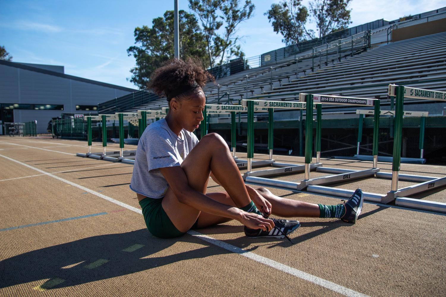 Track+athelete+Khala+Clarke+ties+her+shoelaces+after+her+Thursday+practice.+Clarke+is+a+journalism+major+who+splits+her+time+between+running+track+and+keeping+up+with+her+blog%2C+Evolved+Creativity.