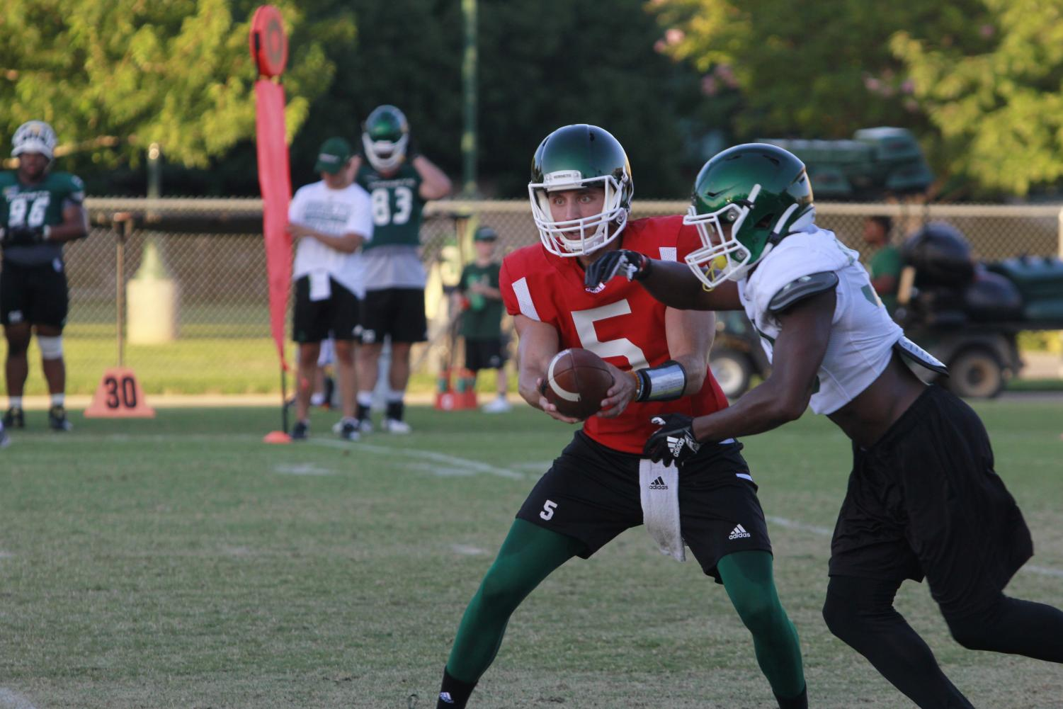 Sac+State+junior+quarterback+Kevin+Thomson+fakes+a+hand-off+to+junior+running+back+Elijah+Dotson+during+training+camp+on+Tuesday%2C+August+12+at+the+practice+field.+Thomson+is+entering+his+third+season+as+starter+for+Sac+State.