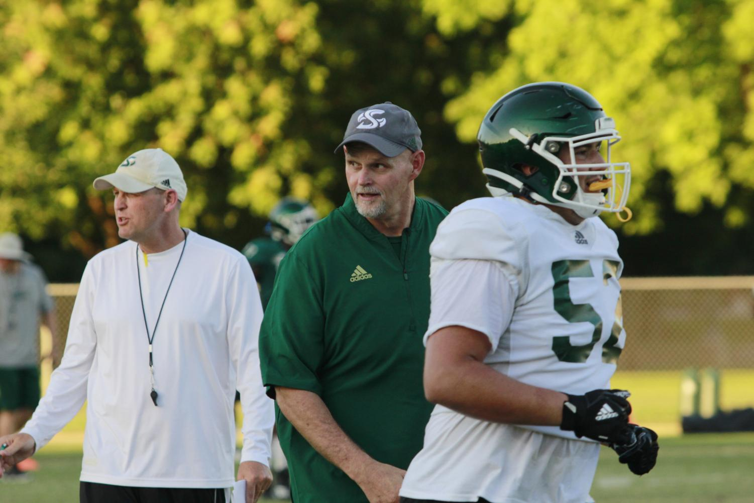 Sac+State+head+coach+Troy+Taylor+and+assistant+head+coach+Kris+Richardson+speak+to+players+during+training+camp+on+Tuesday%2C+August+12+at+the+practice+field.+Richardson+is+one+of+four+coaches+from+Folsom+High+School+that+joined+Taylor%27s+staff.