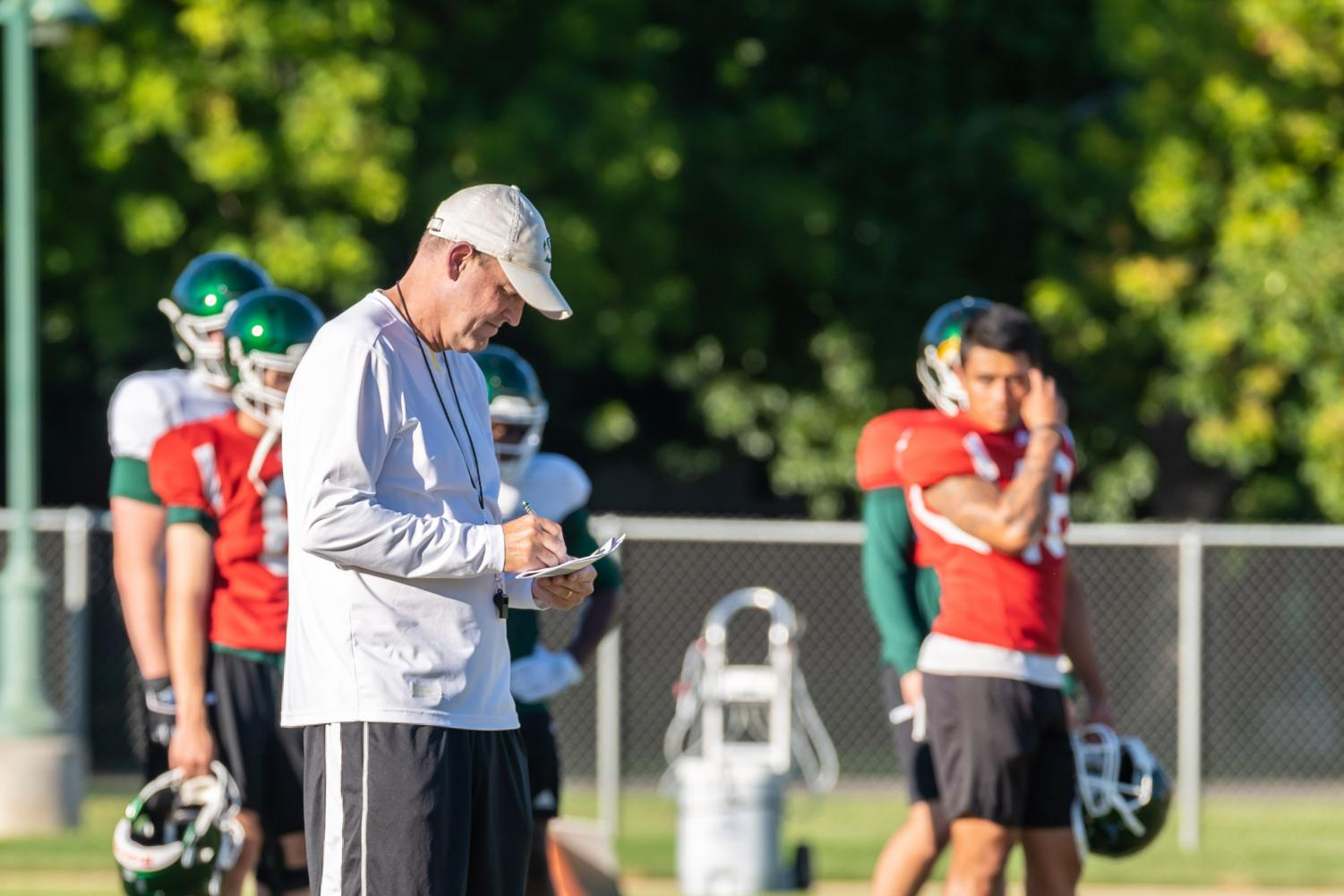 Sac+State+head+coach+Troy+Taylor+takes+notes+during+training+camp+on+Tuesday%2C+August+12+at+the+practice+field.+Taylor+is+entering+his+first+season+at+Sac+State+following+two+years+as+offensive+coordinator+at+the+University+of+Utah.