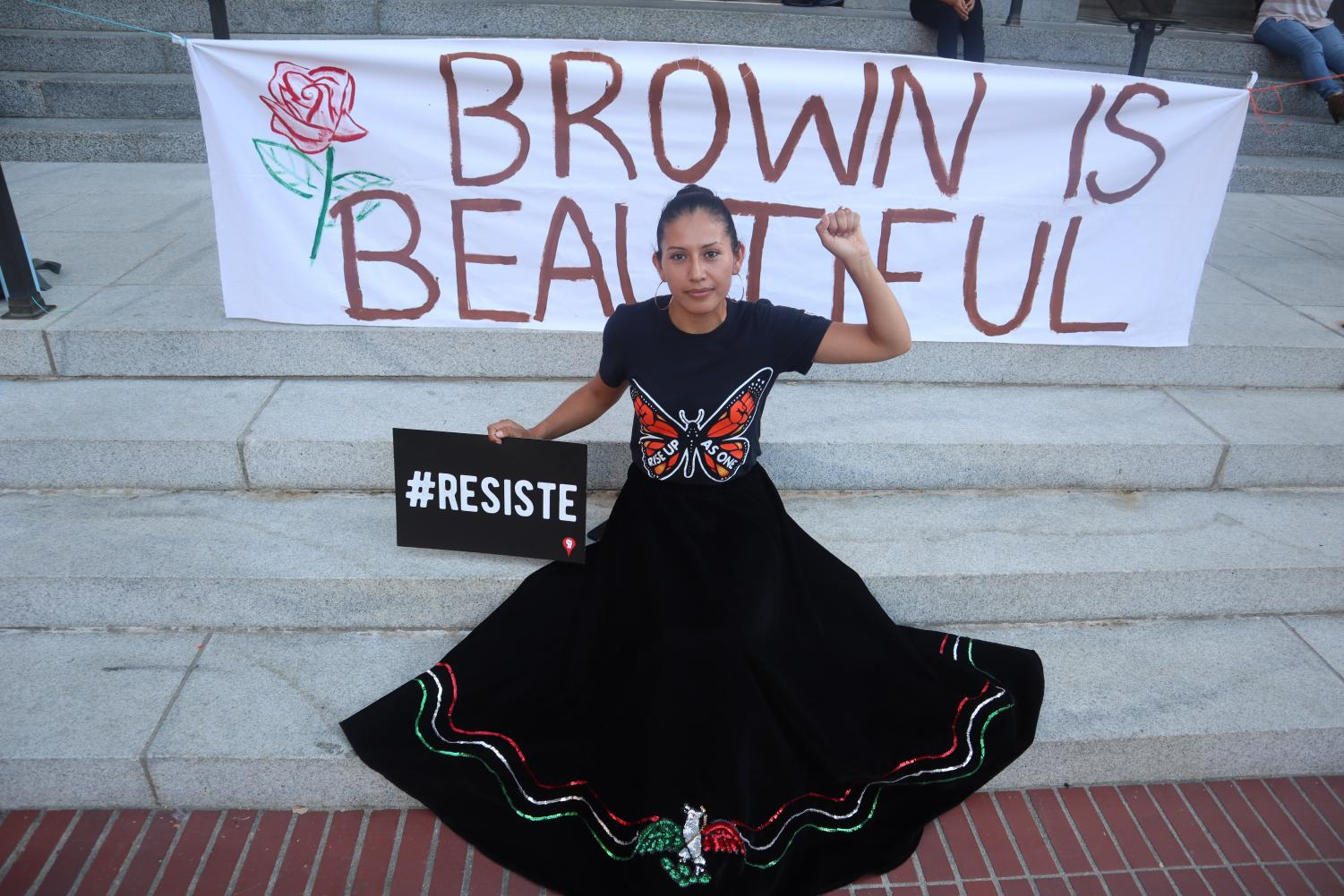 Alma+Lopez%2C+statewide+coordinator+of+Brown+Issues+poses+in+front+of+the+sign+%22Brown+is+Beautiful%22+that+she+painted+along+with+a+political+sign+saying%2C+%22Resist%22+in+Spanish+on+the+California+State+Capitol+steps+on+Tuesday%2C+Sept.+3.