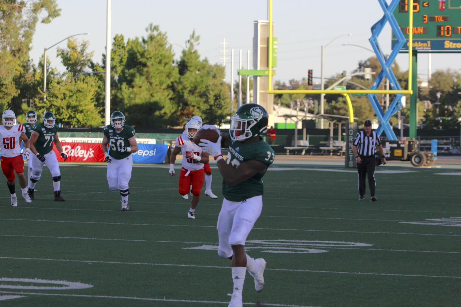 Sac+State+junior+running+back+Elijah+Dotson+catches+a+pass+along+the+sideline+en+route+to+a+touchdown+against+Southern+Oregon+on+Saturday%2C+August+31%2C+at+Hornet+Stadium.+Dotson+had+110+all+purpose+yards+and+three+touchdowns+total.