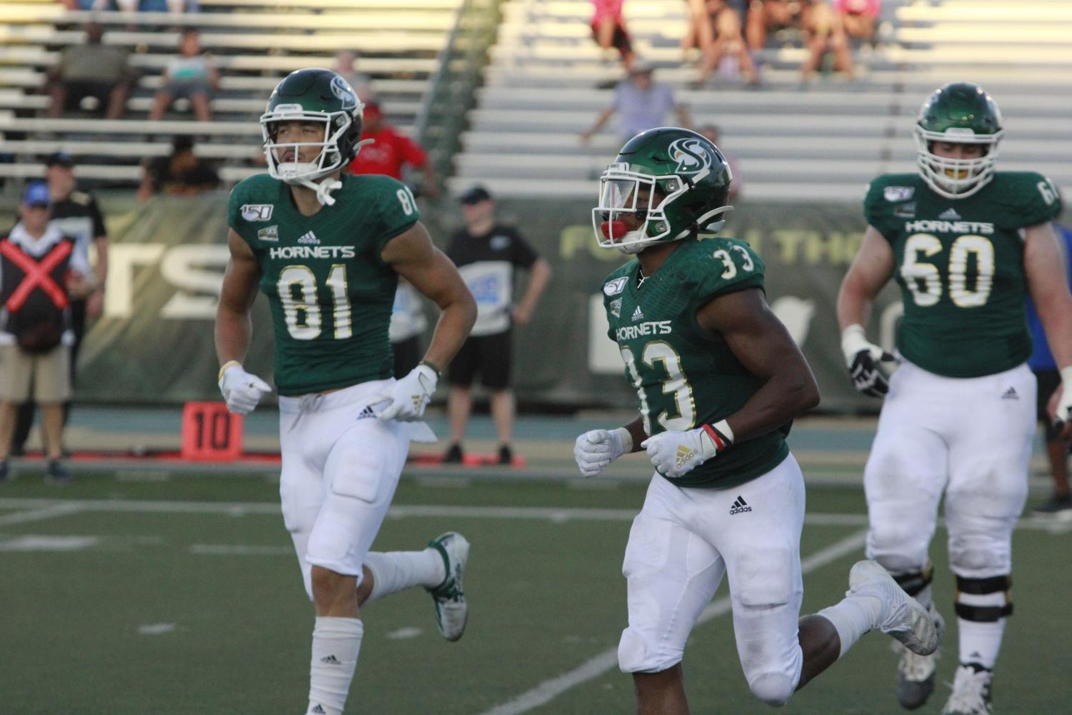 Sac+State+junior+running+back+Elijah+Dotson+and+sophomore+wide+receiver+Tao+McClinton+jog+off+the+field+against+Southern+Oregon+on+Saturday%2C+August+31%2C+at+Hornet+Stadium.+Dotson+had+110+all-purpose+yards+and+three+touchdowns+total.
