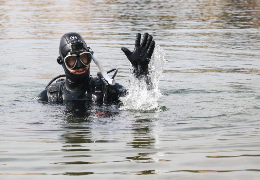 """Sac State student Michael Pelley waves to a passersby as he scuba dives at Lake Natoma on Wednesday, Oct 16.  """"I actually got a picture from a fan that's a picture of me scuba diving, she ended up drawing it while watching one of my videos,"""" Pelley said. """"It's the best piece of treasure i've gotten so far."""""""