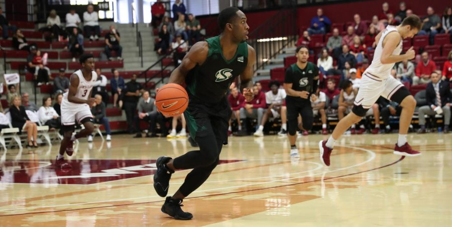 Sac State senior forward Chibueze Jacobs dribbles up court against Santa Clara on Saturday, Dec. 14 at the Leavey Center. The Hornets were defeated by the Broncos 60-58 on Saturday afternoon.