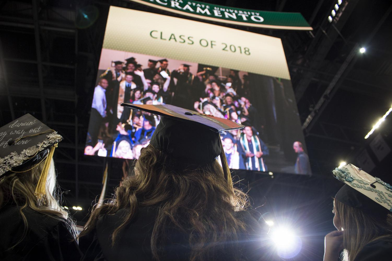 Graduating Sac State students watch themselves on a giant screen inside the Golden 1 Center during commencement on Friday, May 18, 2018. Sac State rose to No. 13 from No. 22 out of 23 CSUs based on 2019 graduation rates, an increase of 127%.