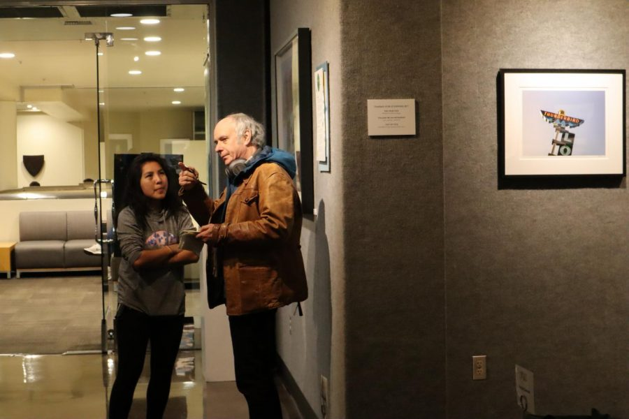 First-year Sac State student Alex Sengbounouvong discusses René Domingo's photographs with another visitor at the opening reception of her