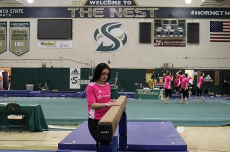 Mariah York poses next to the balance beam before a meet with Alaska Anchorage at the Nest on Sunday, Feb. 16. York has been battling injuries her whole collegiate career and will be out for her entire junior year following ankle surgery.