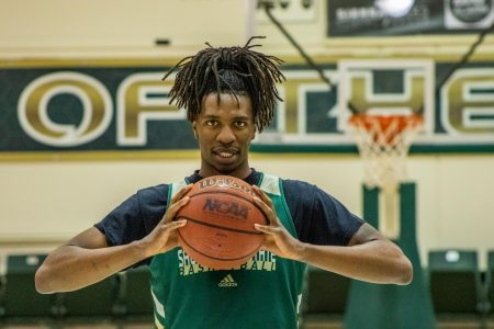 Sac State senior forward Osi Nwachukwu poses with the ball at center court at the Nest on Tuesday, Feb. 25. Nwachukwu has been averaging 6.2 points per game this season.