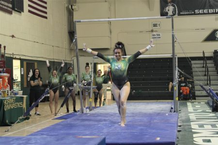 Sac State sophomore Amber Koeth strikes a pose after finishing her routine on the bars Friday, Feb. 28 as her teammates cheer her on in the background at the Nest. The team hopes to place higher at MPSF Championships after placing fifth last season.