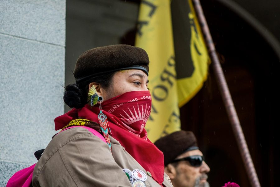 A member of the National Brown Berets stands on the North Steps of the State Capitol on Saturday, March 7, as she listens to speaker Josie Morales talk about the struggles of the women from the East Los Angeles societal chain.