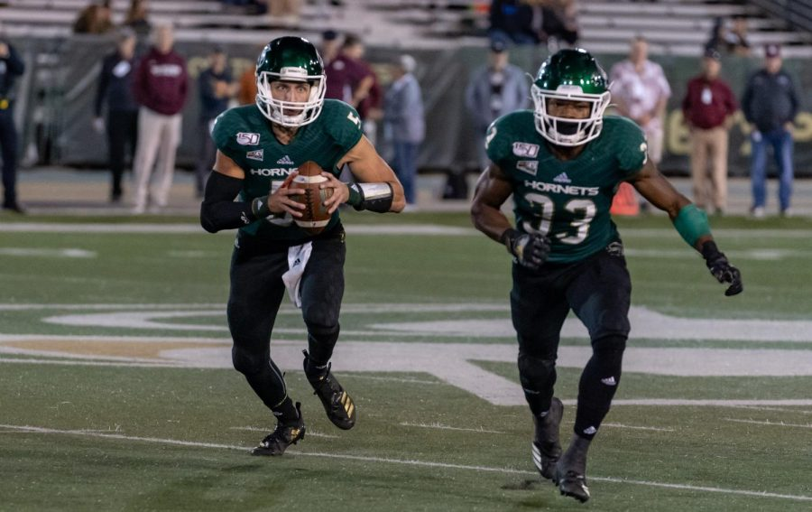 Sac State juniors, quarterback Kevin Thomson and running back Elijah Dotson, run an option play against Montana State on Oct. 19, 2019 at Hornet Stadium. The Hornets main home jersey features a dark green look.