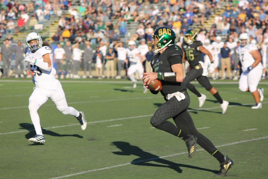 Sac State junior quarterback Kevin Thomson rushes for a first down against UC Davis on Saturday, Nov. 23, 2019 at Hornet Stadium. The hornet on the pants is flying backwards to represent Sac State's alumni.