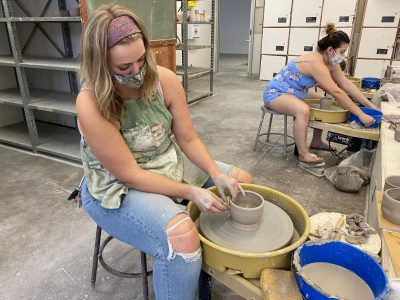 Studio art major Jessica Wolfe and other advanced ceramics students create pottery for their next class project. All students sit at least six feet away from each other at their pottery wheels during class.