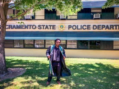 Mulwa James Sumbi poses in front of the Sacramento State Police Department in his graduation robe. Photo courtesy of Jonathan Adorno.