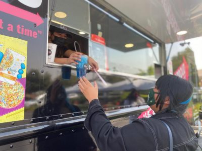 """Employee Gisel Rodriguez hands a """"Mamba"""" lemonade drink to new customer Marie Dominguez on September 8, 2020. The Onit Coffee truck is located in the parking lot of Precision M.D. in Elk Grove, CA."""