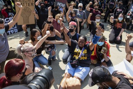 Dionne Smith-Downs, right, of Stockton sits and raises her arms during a Defund the Lodi PD rally in Lodi, California, Saturday, Sept. 5, 2020. Her 16-year-old son James Rivera was shot and killed by a Stockton PD officer.