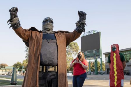 Kyle Lillie, throws coach, dressed as Batman, poses for a photo at the track and field Halloween costume contest at Hornet Stadium Friday, Oct. 30, 2020. The throwers and Coach Lillie dressed as superheroes and everyday heroes.