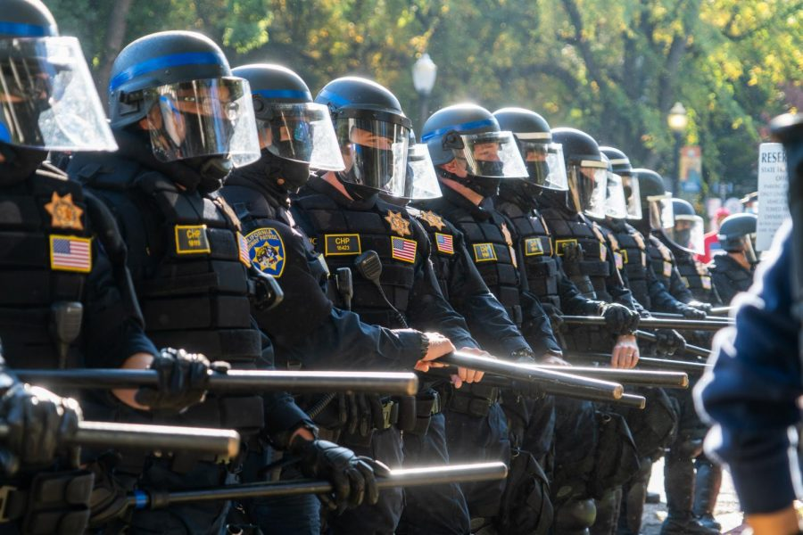 California Highway Patrol officers situated with riot gear and equipped with batons line up near 9th Street and the Capitol Mall in front of groups counter-protesters opposing Trump supporters on Saturday, Nov. 14, 2020. Tensions escalated after counter-protesters and protesters dressed as Proud Boys members clashed on the lawn of the California State Transportation Agency Building.