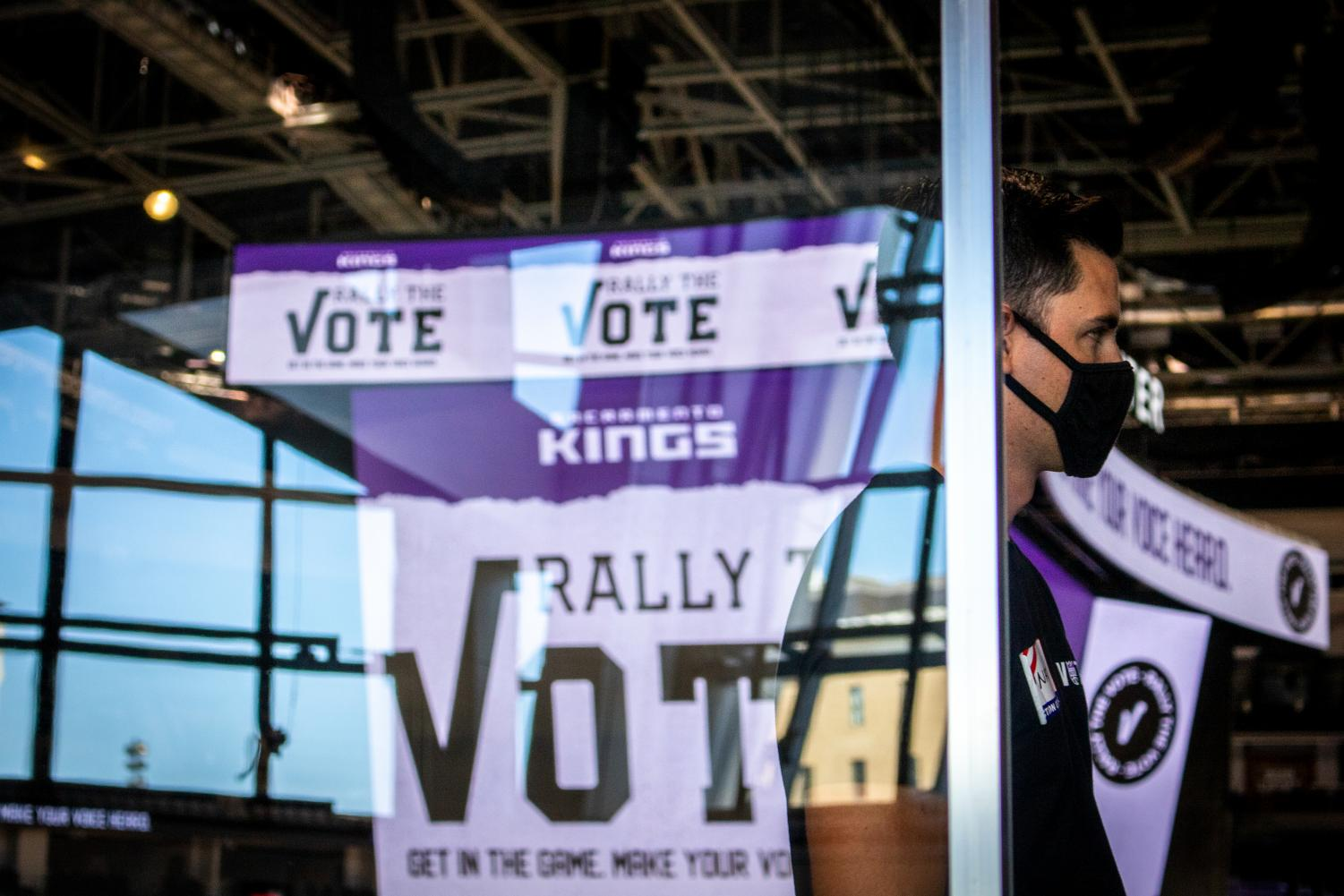 A poll worker stands behind a standing sheet of plexiglass at the Golden 1 Center Tuesday, Nov. 3, 2020. The home of the Sacramento Kings follows social distancing protocols to prevent the spread of COVID-19. (Rahul Lal)