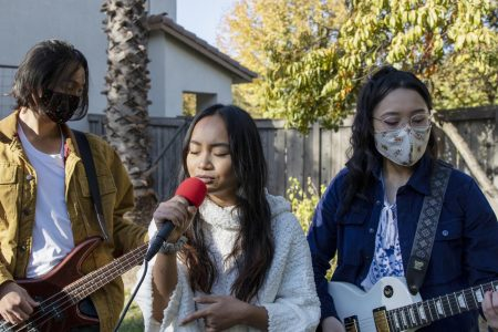 The band Break Up Hoodies performs songs in a backyard in Sacramento, California, Sunday, Nov. 8, 2020. The band includes Sacramento State computer science major Lauren Mateo, center, on vocals, Devyn Farrales, left, on bass and Jasmine Rubio on guitar and keys.