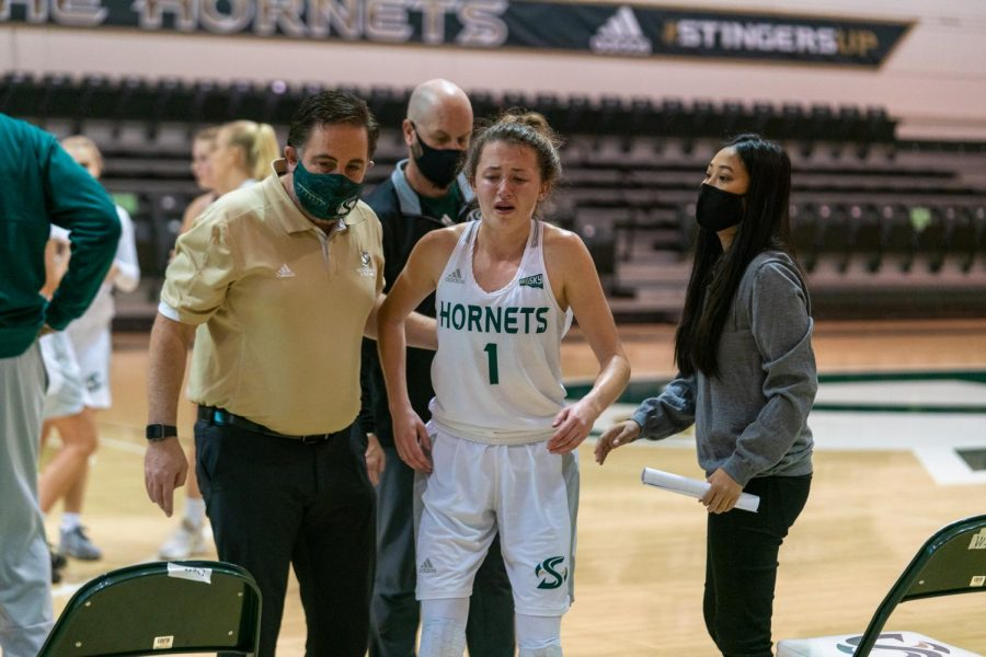 After suffering from an ankle injury on the court, Point Guard Milee Enger stands up and walks to the benches in the first half of Sac State Women's Basketball season opener on December 12, 2020. Enger was unable to return to the court as her team continued with six players.