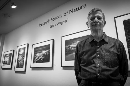"Northern California photographer Gary Wagner poses in front of his ""Iceland: Forces of Nature"" photo gallery at the Viewpoint Photographic Art Center Tuesday, Nov. 15, 2020. Wagner said he prefers to photograph exclusively in black and white  to emphasize that the photos are interpretations."