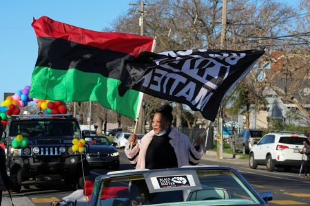 Tanya Faison, founder of BLM Sacramento, holding the BLM and Pan-Africa flag as she leads the Reclaim MLK  car caravan hosted by BLM Sacramento and NAACP Sacramento on Monday, Jan. 18, 2021. The caravan started at Grant High School then proceeded to Sacramento City College, then to Oak Park Community Center and ended at Sacramento State.