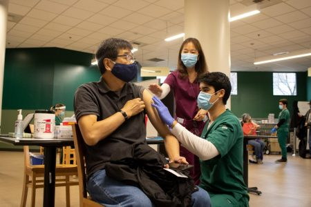 Francis Yuen, faculty in social work, gets injected with his first dose of the COVID-19 vaccine by Austin Friedheim in the Brown Bag room in the Union on Jan. 28, 2021. Sacramento State will send invitations this week for face-to-face faculty and on-campus staff to be vaccinated for COVID-19 according to Sac State President Robert Nelsen.