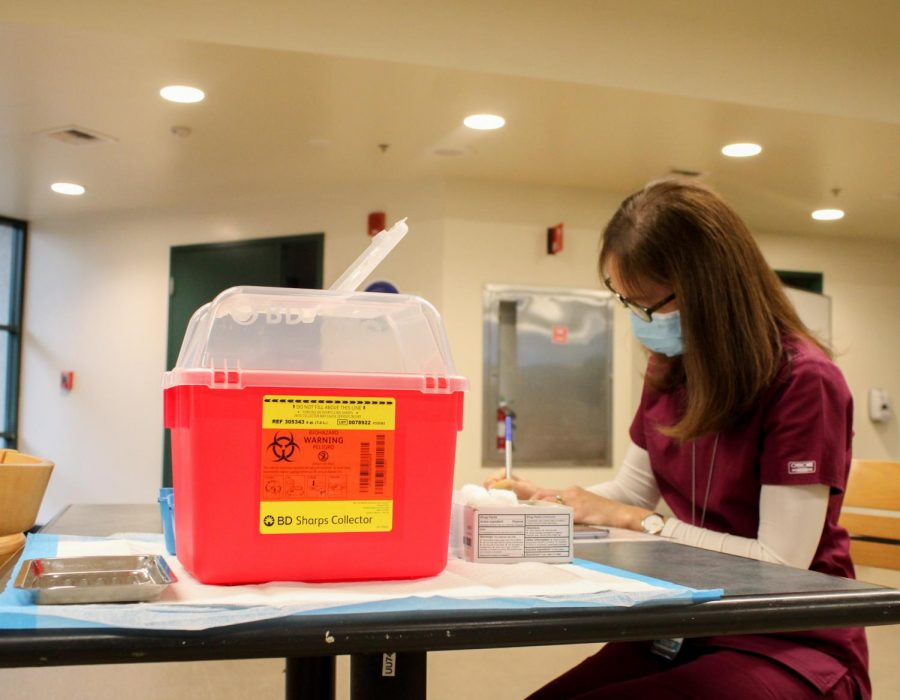 Catherine Nigro, registered nurse for the student health center, prepares for the first doses of the COVID-19 vaccine to be distributed to students and faculty in the in the Brown Bag room in the Union on Thursday, Jan. 28, 2021. They started preparing the vaccines at 8 a.m. and started distributing at 9 a.m.