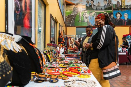 "Eunice Kaesa, owner of African Hats and Fashion, sells a set of earrings to Simone at the African Market Place on Saturday Feb. 20, 2021. She describes her table as the ""woman confusion zone,"" mentioning that several women who pass by this location, ""don't know what to get and what not to get."""