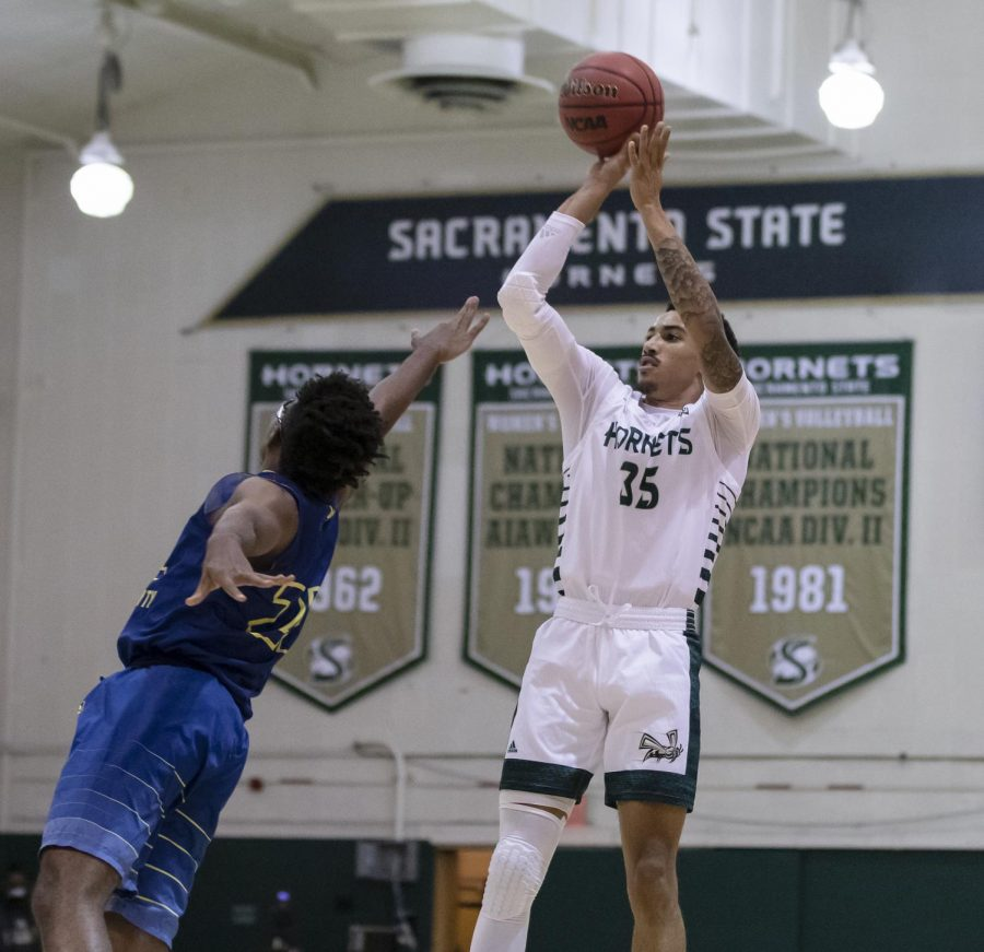 Sac State's Christian Terrell (35) shoots a 3-pointer over Bethesda's Gabriel Bazile (22) during the first half in the game against Bethesda University at The Nest at Sac State Wednesday, Nov. 25, 2020. This is Terrell's second back from injury and he led the team with three steals in the loss.