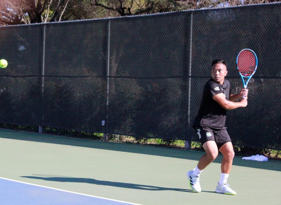 Senior Hermont Legaspi in the middle of a volley during his singles game at the campus tennis courts Wednesday, Feb. 10, 2021. The Hornets were defeated by the Dons 6-1 after failing to win any singles matches.