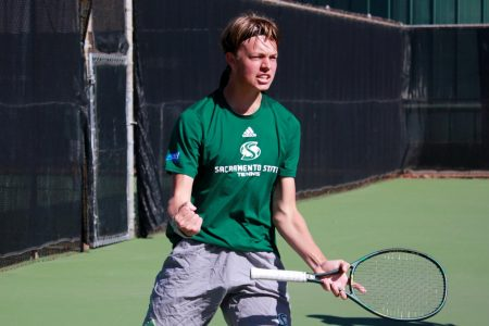 Freshman Liam Liles celebrates after scoring in the first set of his doubles matchup at the campus tennis courts Friday, Feb. 12. The Hornets fell to the Mustangs 4-0.