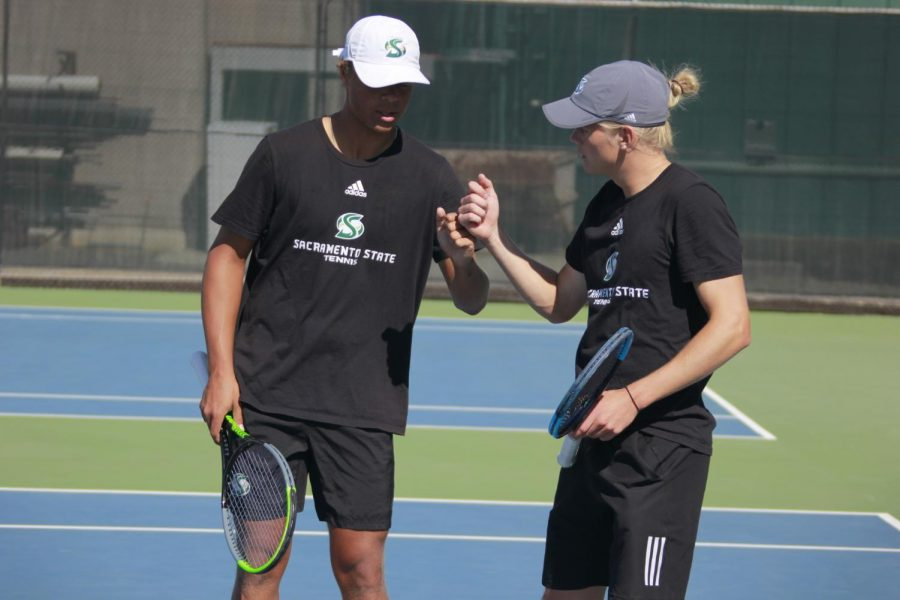 Freshmen+Rudolfs+Aksenoks+and+Jan+Silva+fist+bumping+during+their+doubles+set+against+Saint+Mary%E2%80%99s+Friday%2C+March+12%2C+at+the+Sac+State+tennis+courts.+The+men%E2%80%99s+tennis+team+lost++the+match+4-1.+%0A