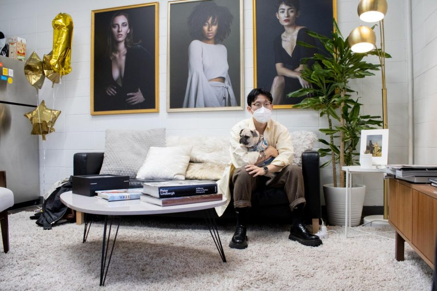 Professional photographer and Tik Tok user David Suh sits on a couch with his dog Maya inside his studio on Tuesday, Feb. 16, 2021. Maya is a pug and 1.5 years old.