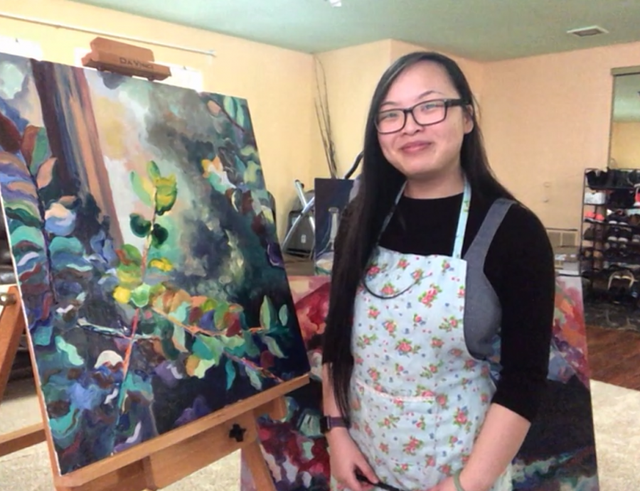 Michelle Yee sits next to her artwork in her living room on Friday, Feb. 26, 2021. During isolation, Yee said she prefers to spend her time painting as a way to cope with the sorrow of missing out on creating memories with friends.