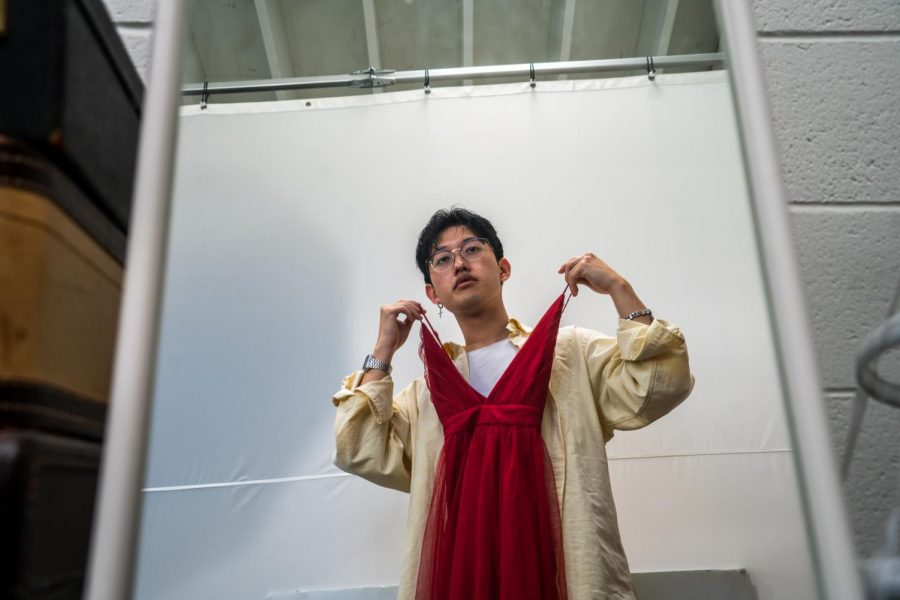 TikTok celebrity and Sacramento photographer David Suh poses at his studio Feb. 16, 2021 with one of the many dresses used in his TikTok videos. David tries to challenge preconceived notions of femininity and masculinity in his videos by dressing up and re-enacting the experiences he has with clients.