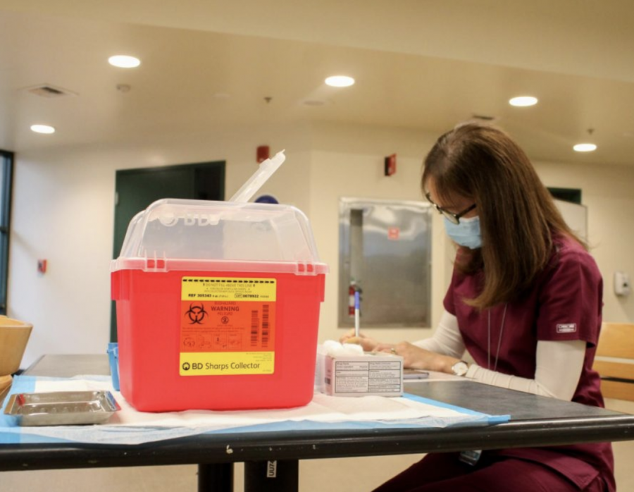 FILE PHOTO: Catherine Nigro, registered nurse for the student health center, prepares for the first doses of the COVID-19 vaccine to be distributed to students and faculty in the Brown Bag room in the Union on Jan. 28, 2021. Sacramento County entered the red tier of COVID-19 restrictions Tuesday, allowing some businesses to open indoors with modifications, according to California's COVID-19 informational website.