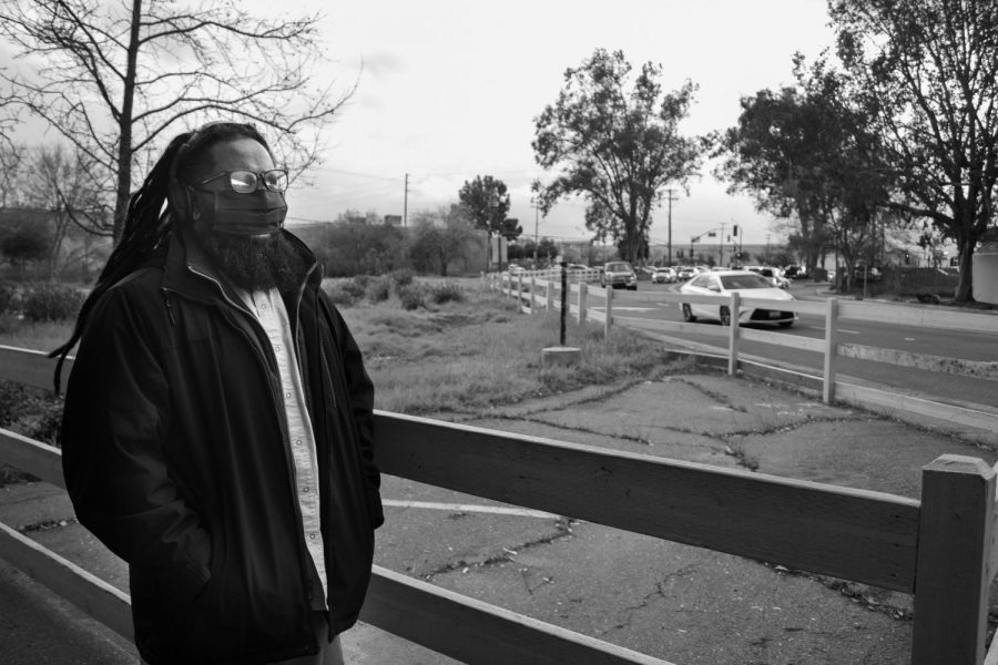 Charles Joseph walks to the edge of his apartment complex's parking lot to his favorite spot to watch life unfold on Wednesday, March 10, 2021 in Sacramento, California. His scenery from here includes an old wilted oak tree, an empty field that used to be apartments and a Dutch Bros coffee shop with a constantly filled drive-thru line.