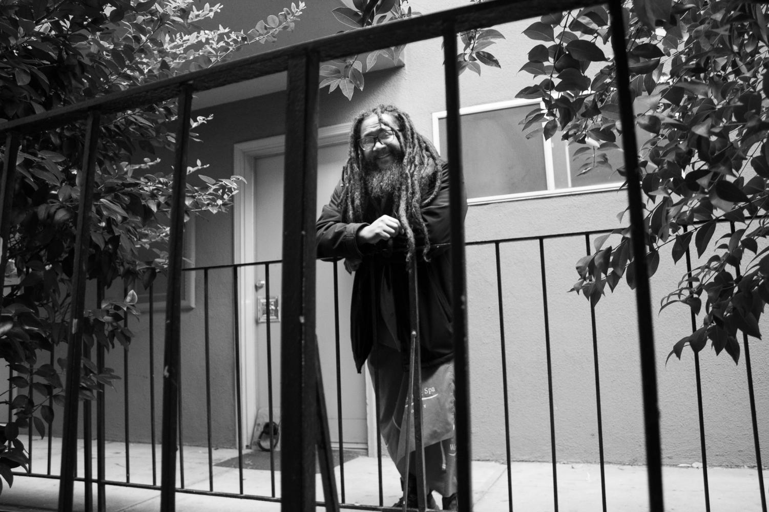 Charles Joseph stands outside of his second story apartment next to trees growing in between two apartment buildings Wednesday, March 10, 2021 in Sacramento, California. Joseph said that he enjoys how calm and peaceful his apartment is after years of living in prisons and detainment centers.