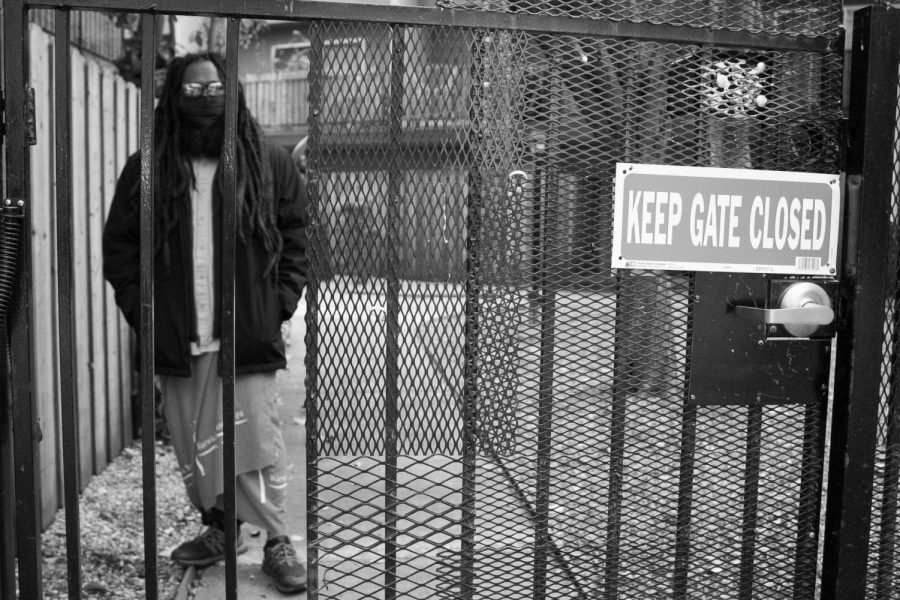 Joseph stands on the opposite side of a gate to the pool area that has been closed since the start of the COVID-19 pandemic on Wednesday, March 10, 2021 in Sacramento, California. Although he is experiencing the most freedom he has had in years, Joseph is still confined to Sacramento County through the ankle monitor on his right foot that only allows him to travel 50 miles from his home.