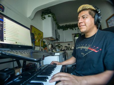 DJ/promoter/music artist Alex Hernandez, 30, has his equipment setup in the kitchen of his studio apartment downtown Sacramento. He records and plays keyboard digitally with software that allows him to plug-in sounds of other instruments. Here, Hernandez is playing with a synthesizer plug-in Saturday, April 10, 2021.  (Robert J Hansen)