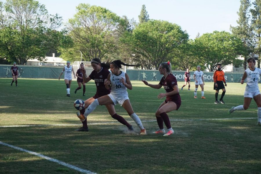 Senior forward Tiffany Miras kicks toward the sidelines as two Montana players fight for control of the ball during the game at Sac State on Friday, April 2. The game was the first Sac State athletic event  to feature fans in attendance, at 20% capacity.