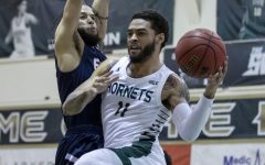 Sacramento State's Brandon Davis (11) passes the ball around Fresno Pacific A.J. Kirby (3) during the second half in the non-conference game at the Nest at Sac State in Sacramento, California, Jan. 3, 2021. Davis is going pro overseas to be the newest point guard to be signed onto the Mets de Guaynabo basketball team.