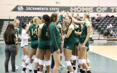 The Sacramento State women's volleyball team huddles with their stingers up during a timeout in a game against CSU Northridge in  the Sacramento State invitational tournament on Sept. 10, 2021. The team lost both of their first Big Sky conference games over the weekend, 2-3 in the first match against Idaho State and 1-3 in its match against Weber State.