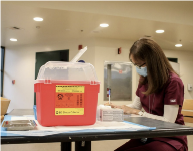 """FILE PHOTO: Catherine Nigro, registered nurse for the Student Health Center, prepares for the first doses of the COVID-19 vaccine to be distributed to students and faculty in the Brown Bag room in the Union on Jan. 28, 2021. Sac State Vice President of Student Affairs Ed Mills said that professors have """"not yet"""" been emailed a list of their students who missed the COVID-19 vaccine certification deadline."""