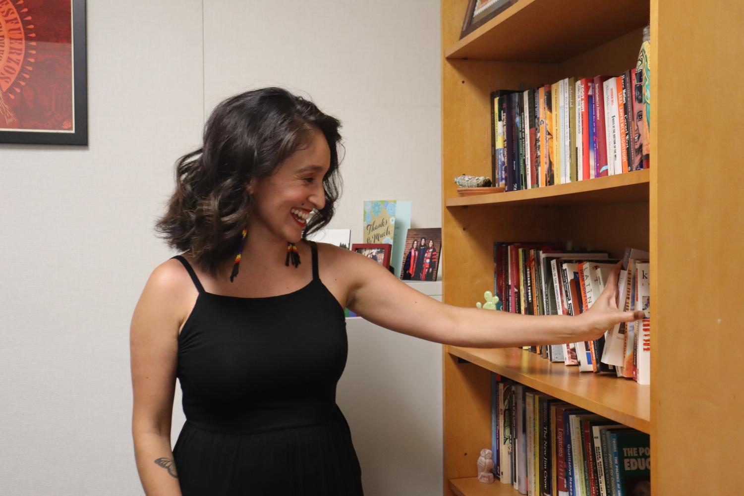 Education assistant professor Alma Flores pulls out a book from her library in her office at Sacramento State on Sept. 7, 2021.Flores said that on her first day of orientation she was one of four or two faculty Chicana out of 80 faculty.